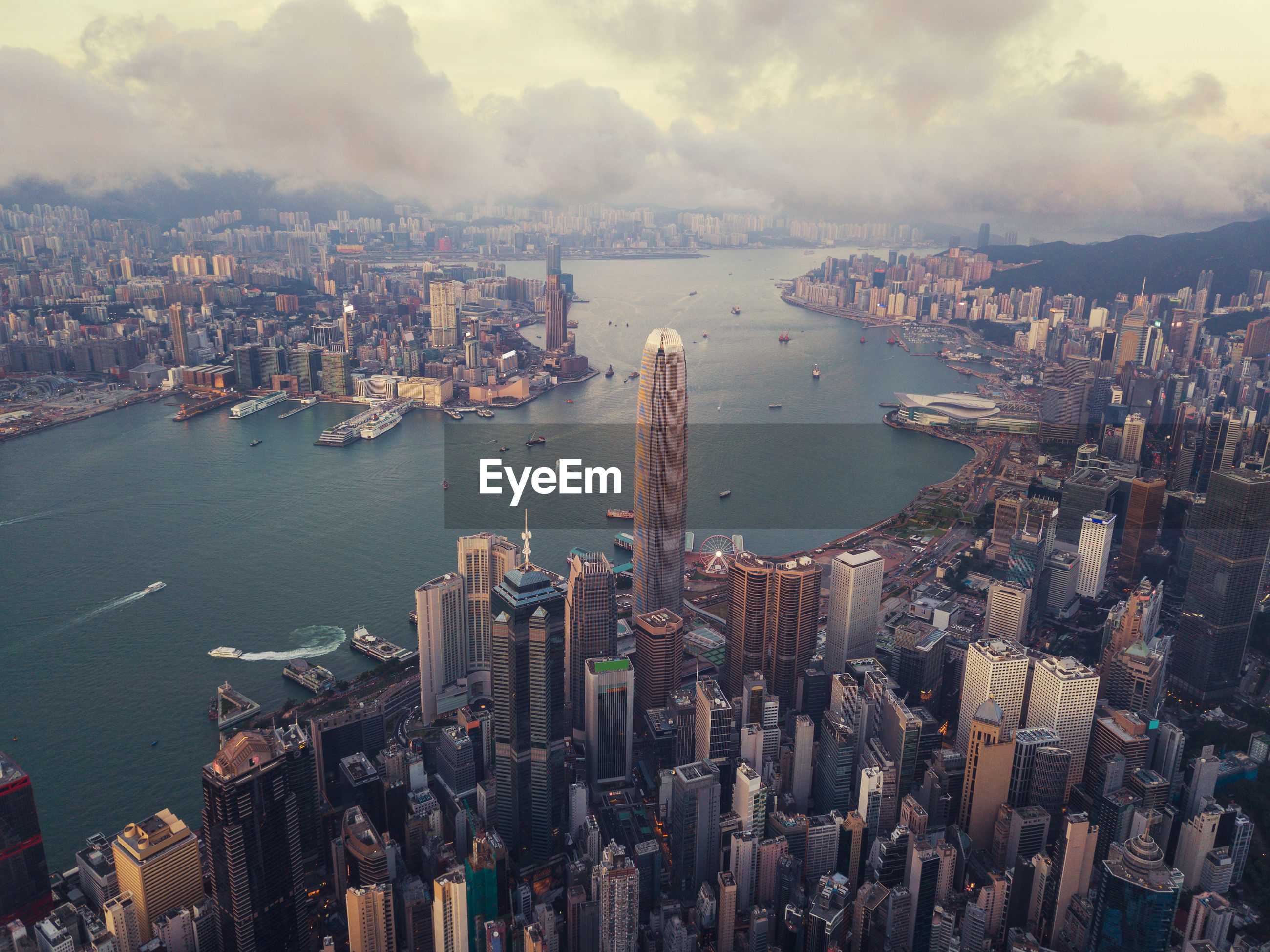 Aerial view of modern buildings in city against cloudy sky