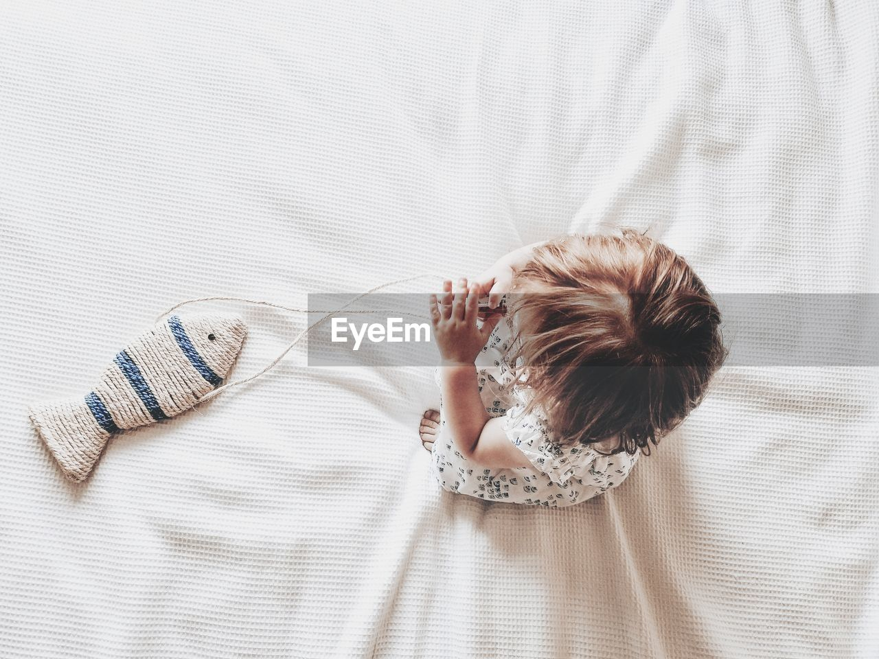 High angle view of baby toddler girl on bed with fish playing