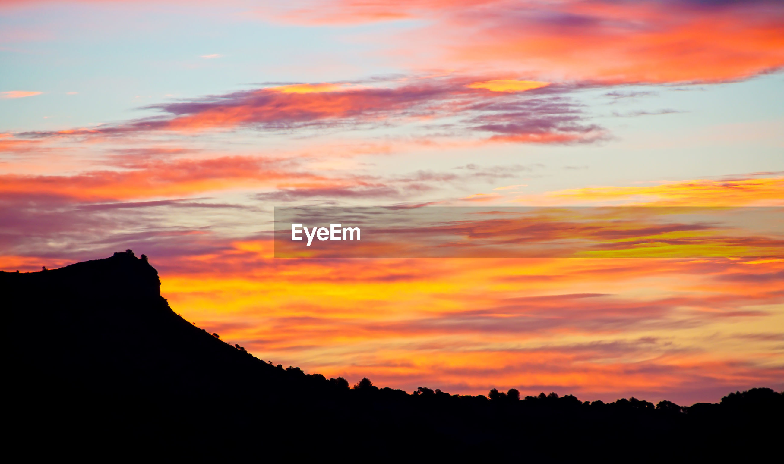 LOW ANGLE VIEW OF SILHOUETTE MOUNTAIN AGAINST ORANGE SUNSET SKY