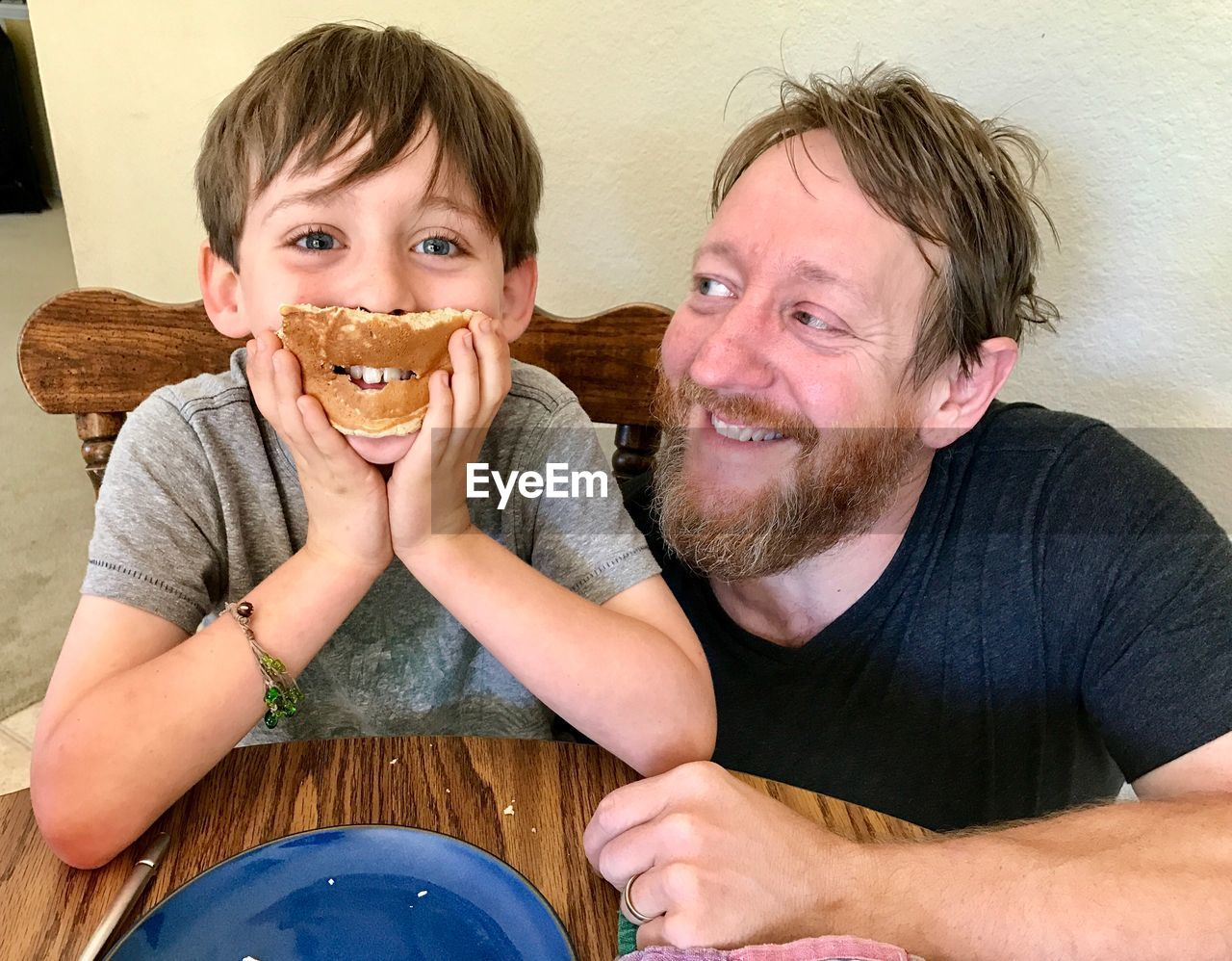 Close-Up Of Boy Eating Food With Father At Table