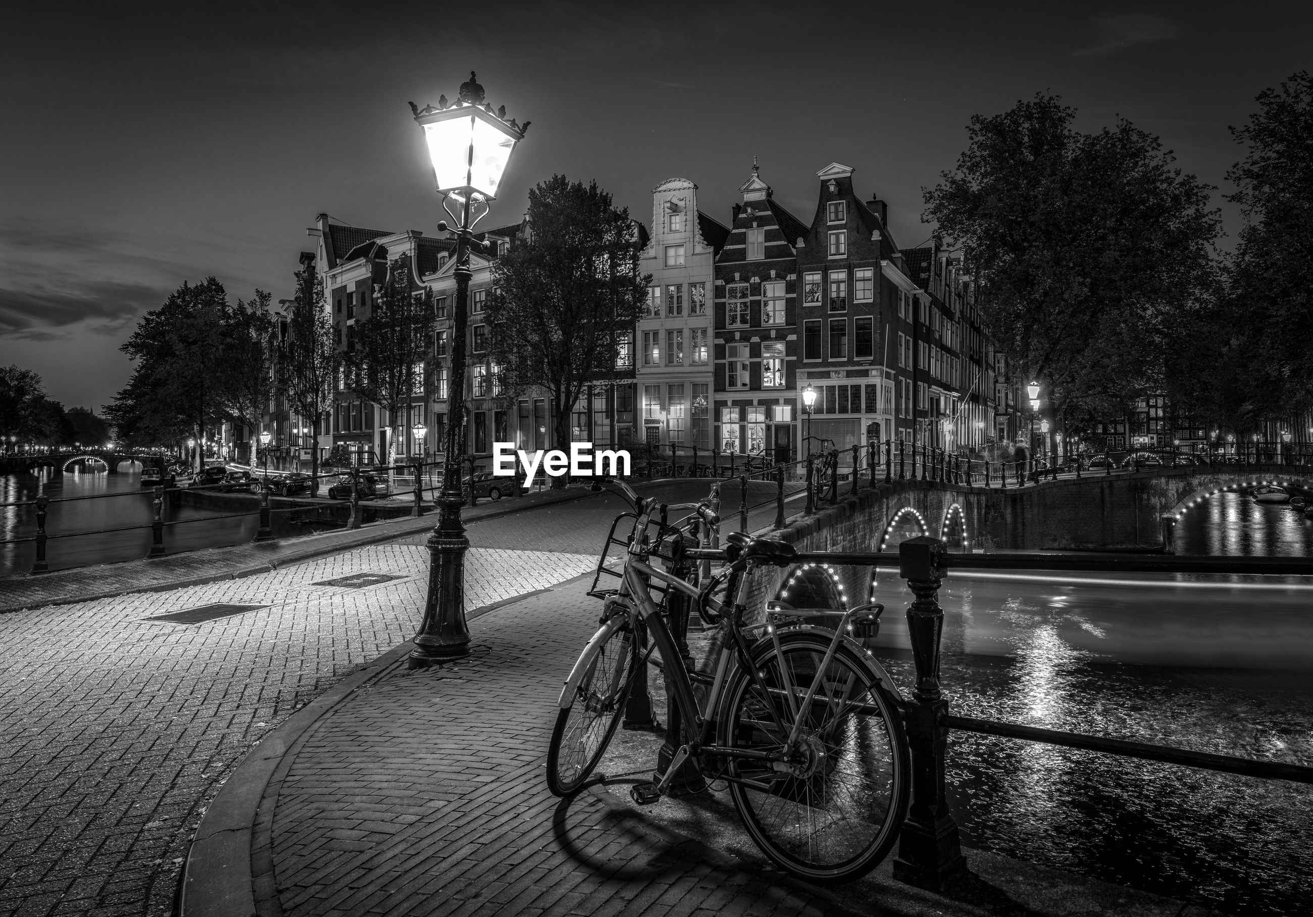Illuminated street by buildings against sky at night amsterdam