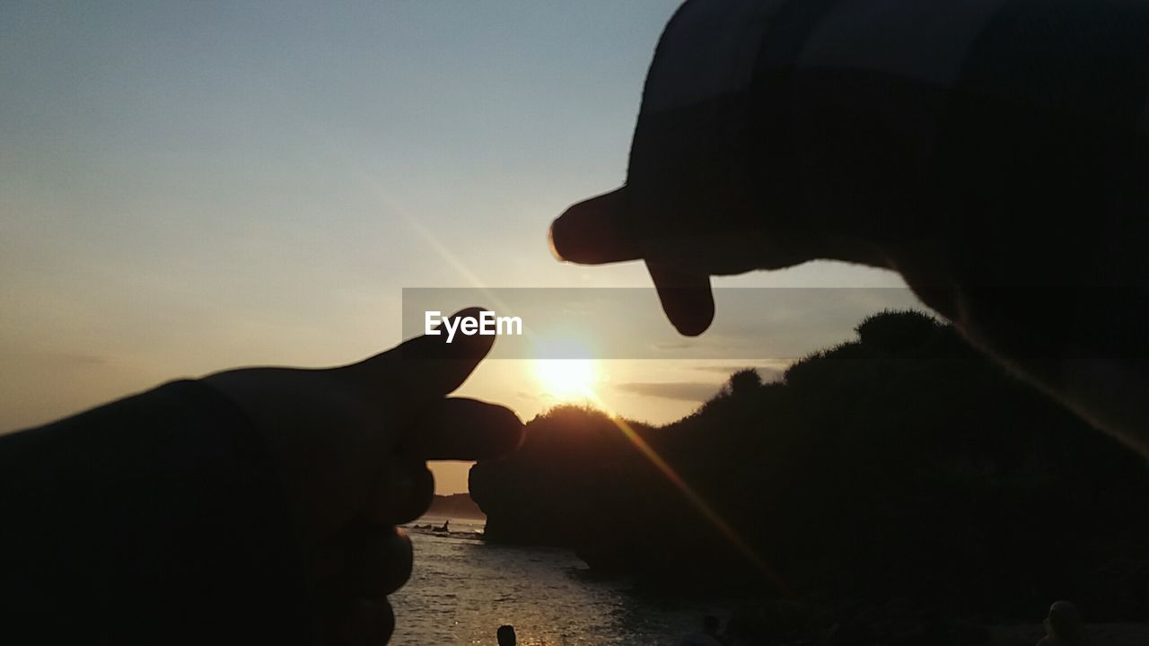 sunset, human hand, silhouette, human finger, sun, sky, human body part, nature, beauty in nature, sea, outdoors, real people, sunlight, close-up, water, scenics, one person, optical illusion, horizon over water, day, people