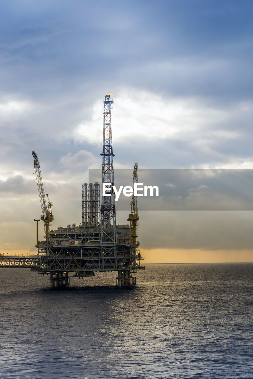 industry, water, sky, oil industry, cloud - sky, sea, offshore platform, drilling rig, fuel and power generation, waterfront, nature, horizon over water, no people, machinery, horizon, crane - construction machinery, outdoors, built structure