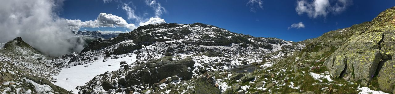 mountain, sky, beauty in nature, snow, cold temperature, cloud - sky, scenics - nature, winter, tranquility, mountain range, tranquil scene, nature, day, snowcapped mountain, low angle view, non-urban scene, no people, plant, panoramic, mountain peak, outdoors, formation
