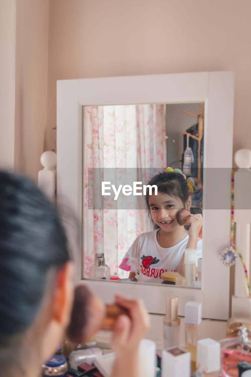 Beautiful little girl plays doing makeup
