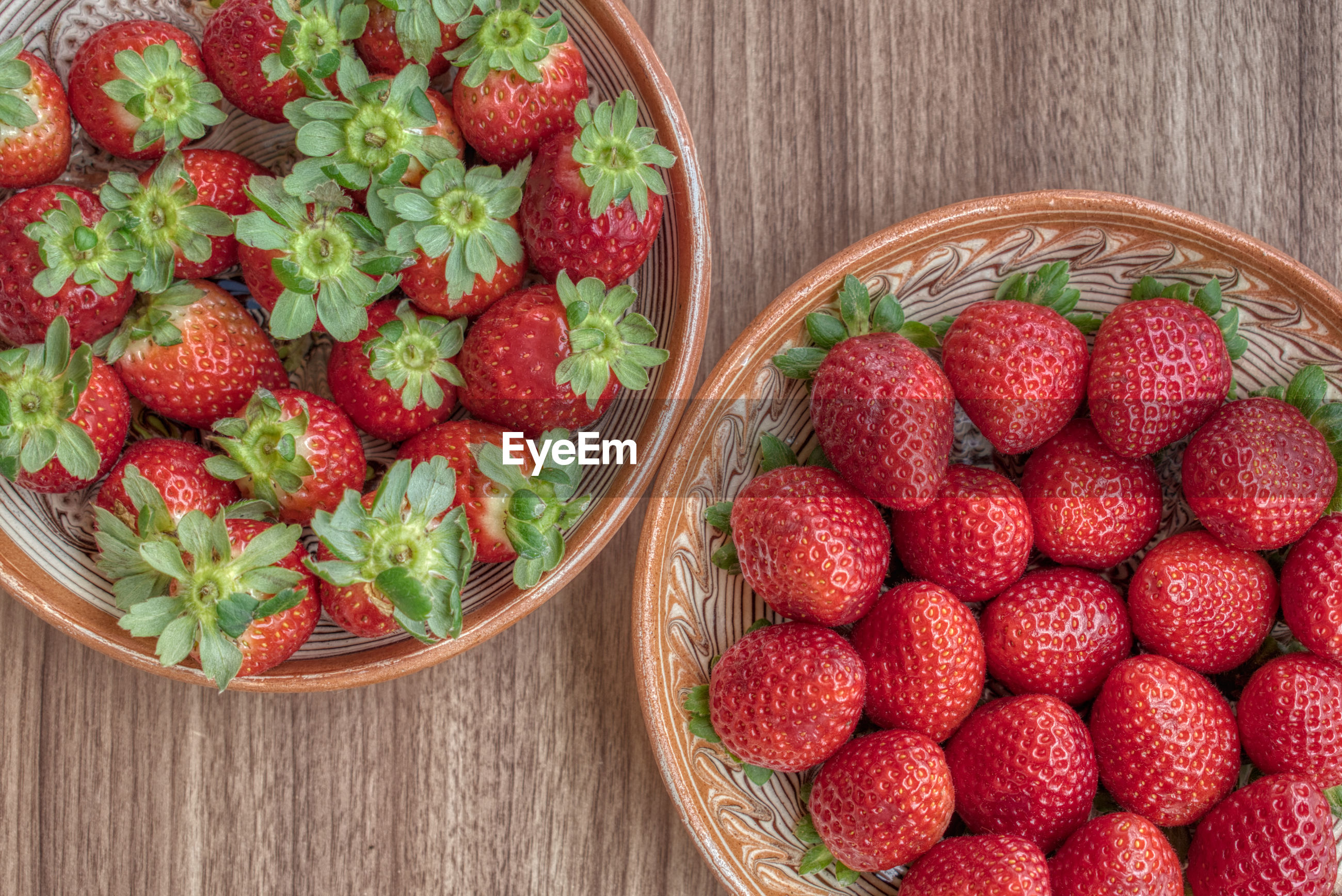 Fresh strawberry in a clay plate on wooden table