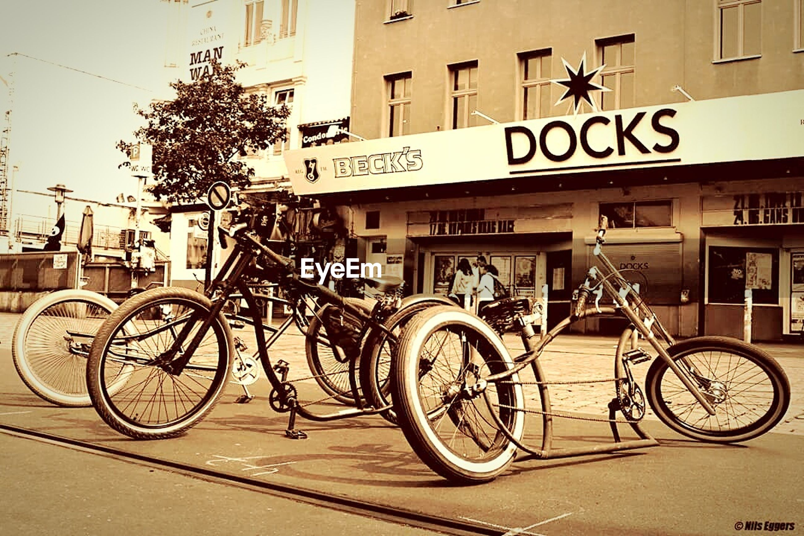 bicycle, text, western script, transportation, mode of transport, land vehicle, building exterior, outdoors, architecture, communication, built structure, stationary, day, city, road sign, no people, sky