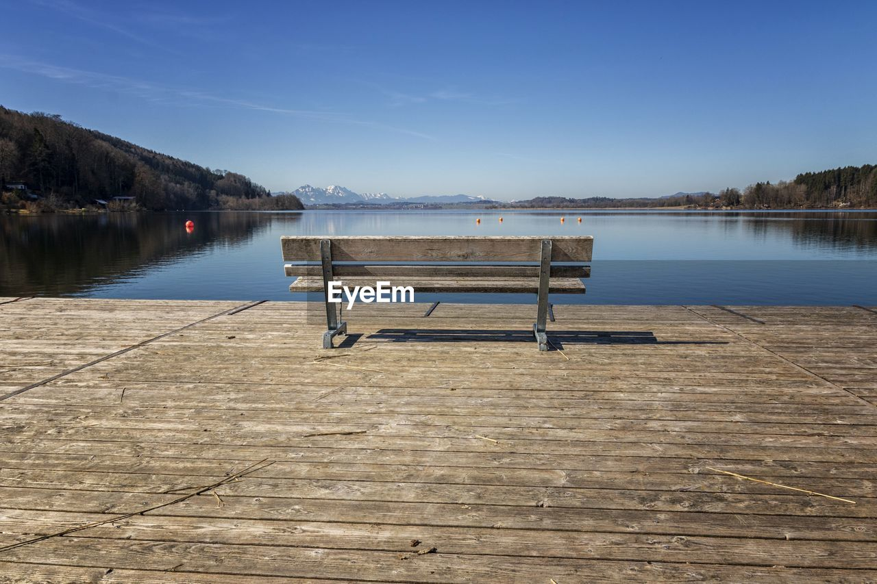 EMPTY PIER ON LAKE AGAINST SKY