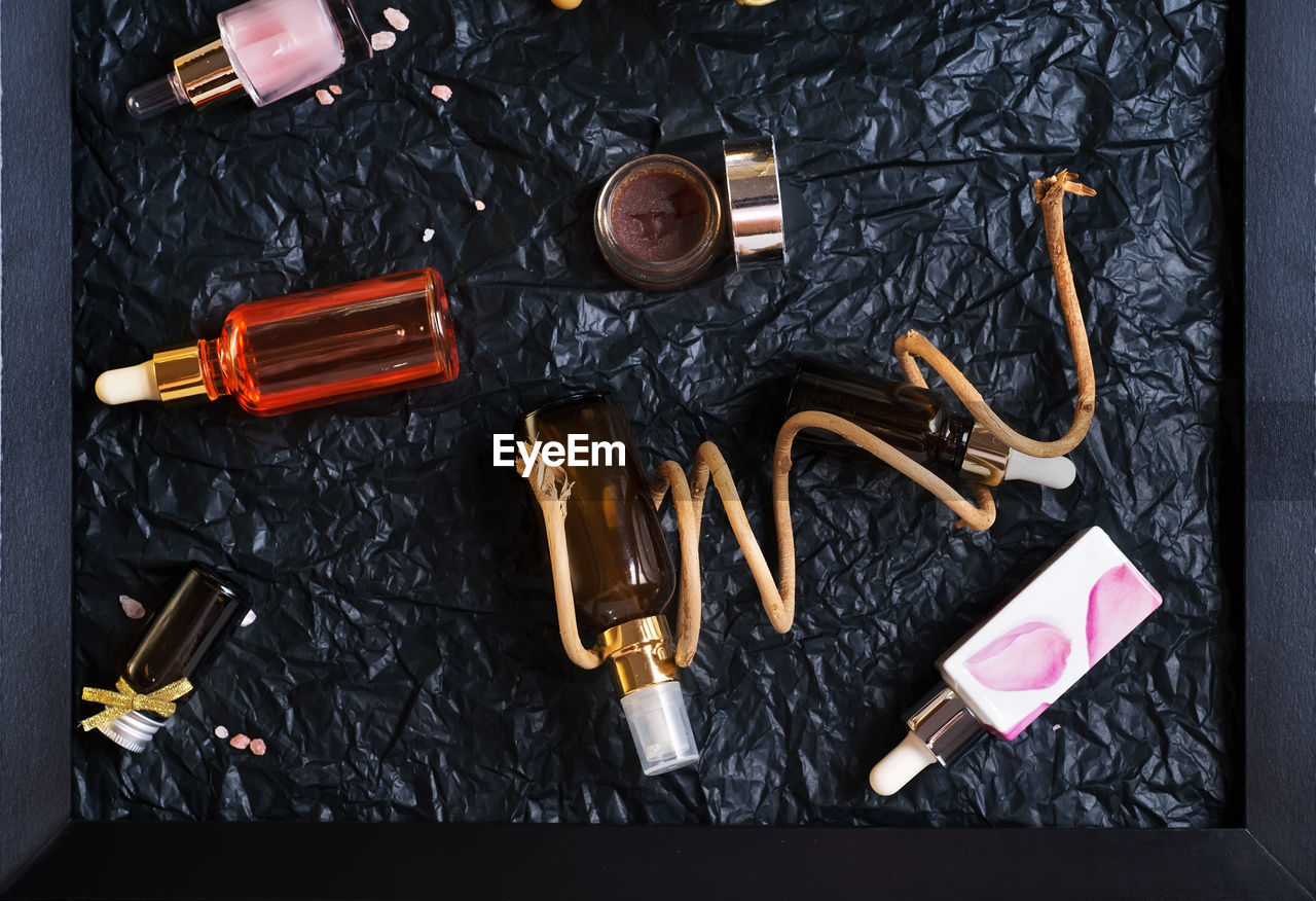 indoors, large group of objects, directly above, still life, high angle view, variation, no people, choice, container, black color, bottle, make-up, fashion, close-up, work tool, metal, body care, table, group of objects, personal accessory