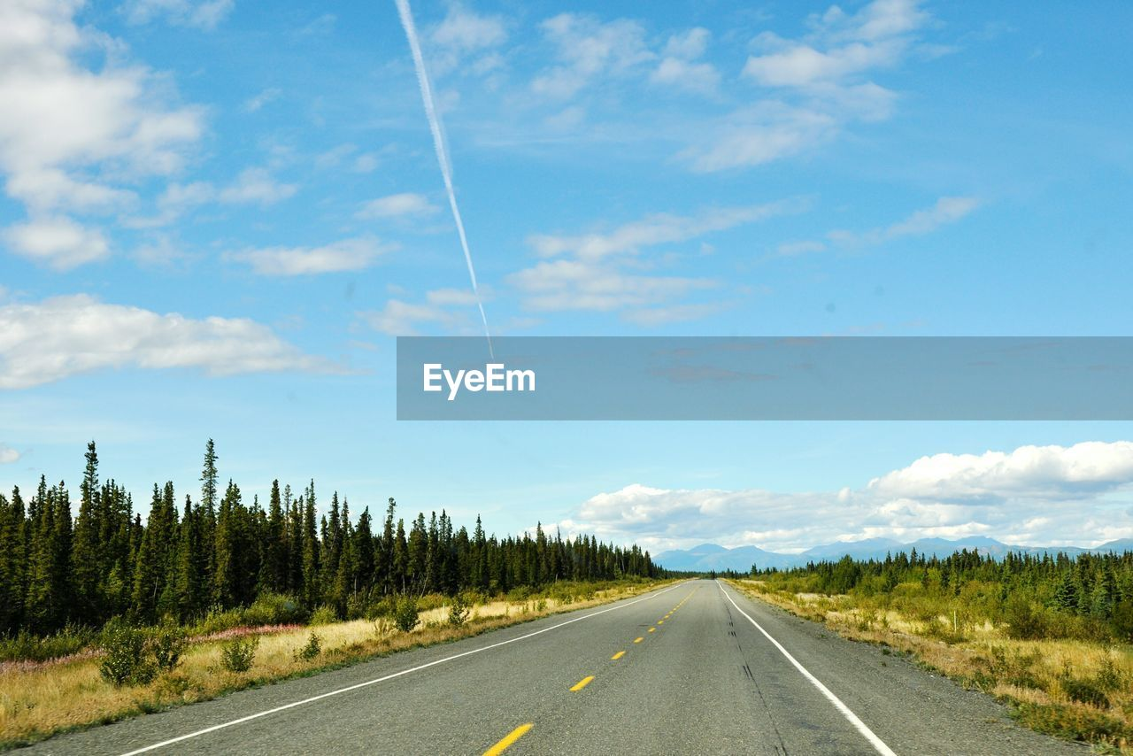 sky, cloud - sky, road, the way forward, direction, transportation, plant, nature, beauty in nature, no people, road marking, landscape, tranquil scene, tree, marking, symbol, non-urban scene, tranquility, day, diminishing perspective, outdoors, dividing line, vapor trail