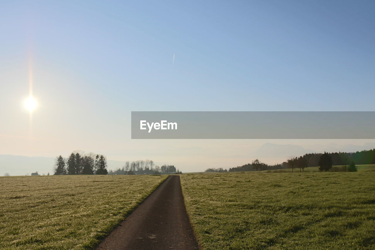 field, sky, landscape, scenics, the way forward, nature, grass, tranquil scene, tranquility, clear sky, no people, beauty in nature, sun, outdoors, transportation, rural scene, tree, road, day