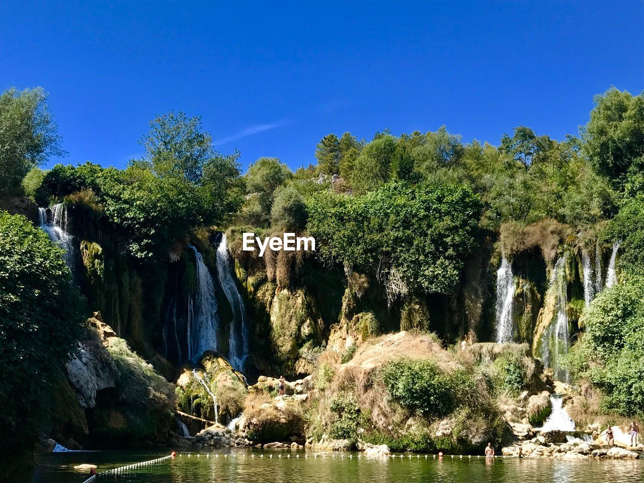water, tree, plant, scenics - nature, beauty in nature, nature, sky, waterfall, growth, day, no people, tranquility, river, tranquil scene, blue, clear sky, forest, sunlight, rock, outdoors, flowing water, flowing