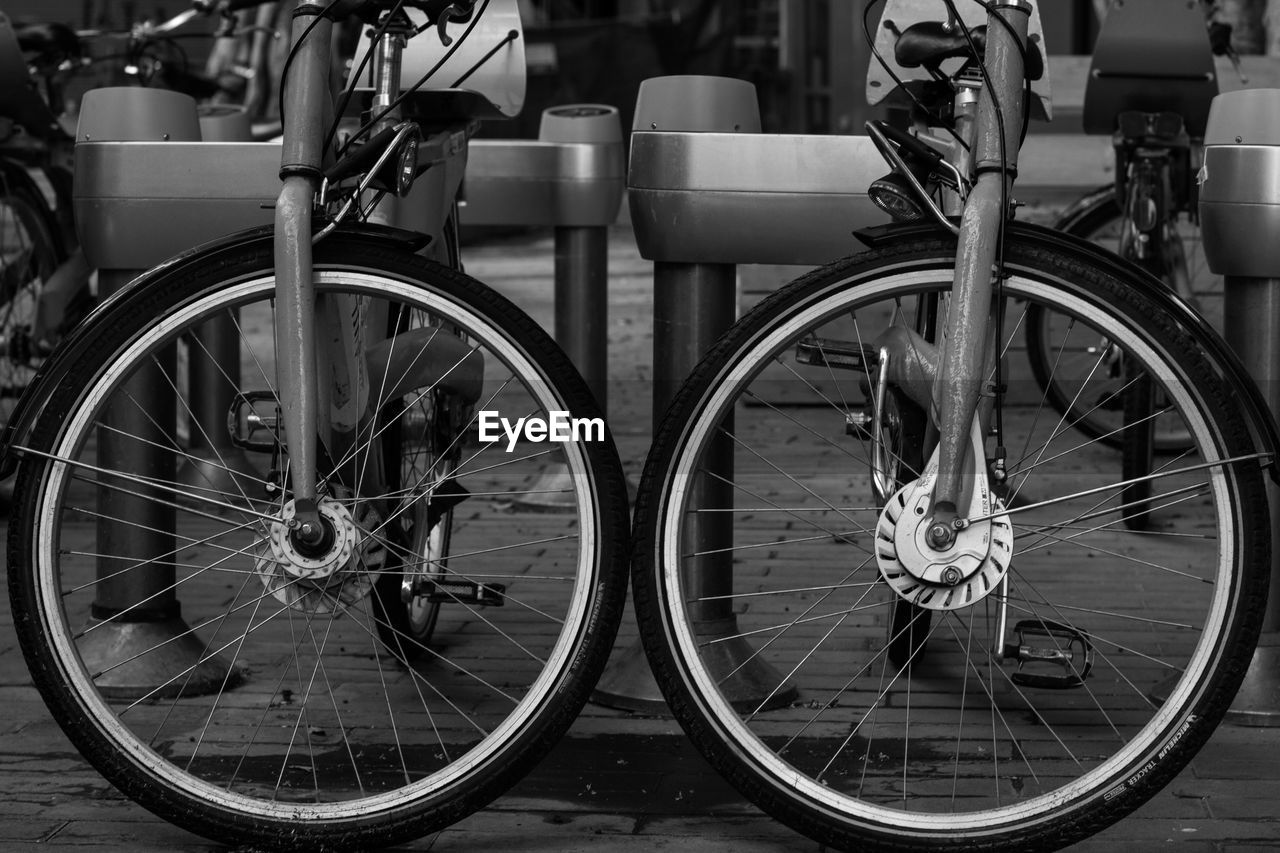 transportation, mode of transportation, bicycle, land vehicle, no people, day, wheel, city, focus on foreground, outdoors, street, reflection, travel, glass - material, footpath, architecture, close-up, stationary, public transportation, spoke