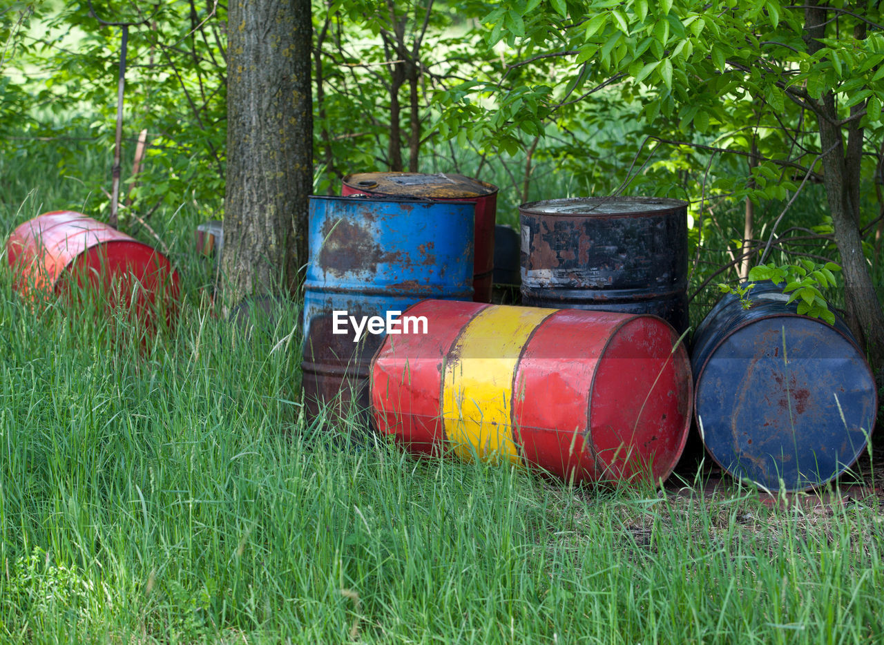 grass, barrel, outdoors, drum - container, field, day, tree, green color, red, no people, landscape, oil industry, multi colored, nature, wine cask, oil pump