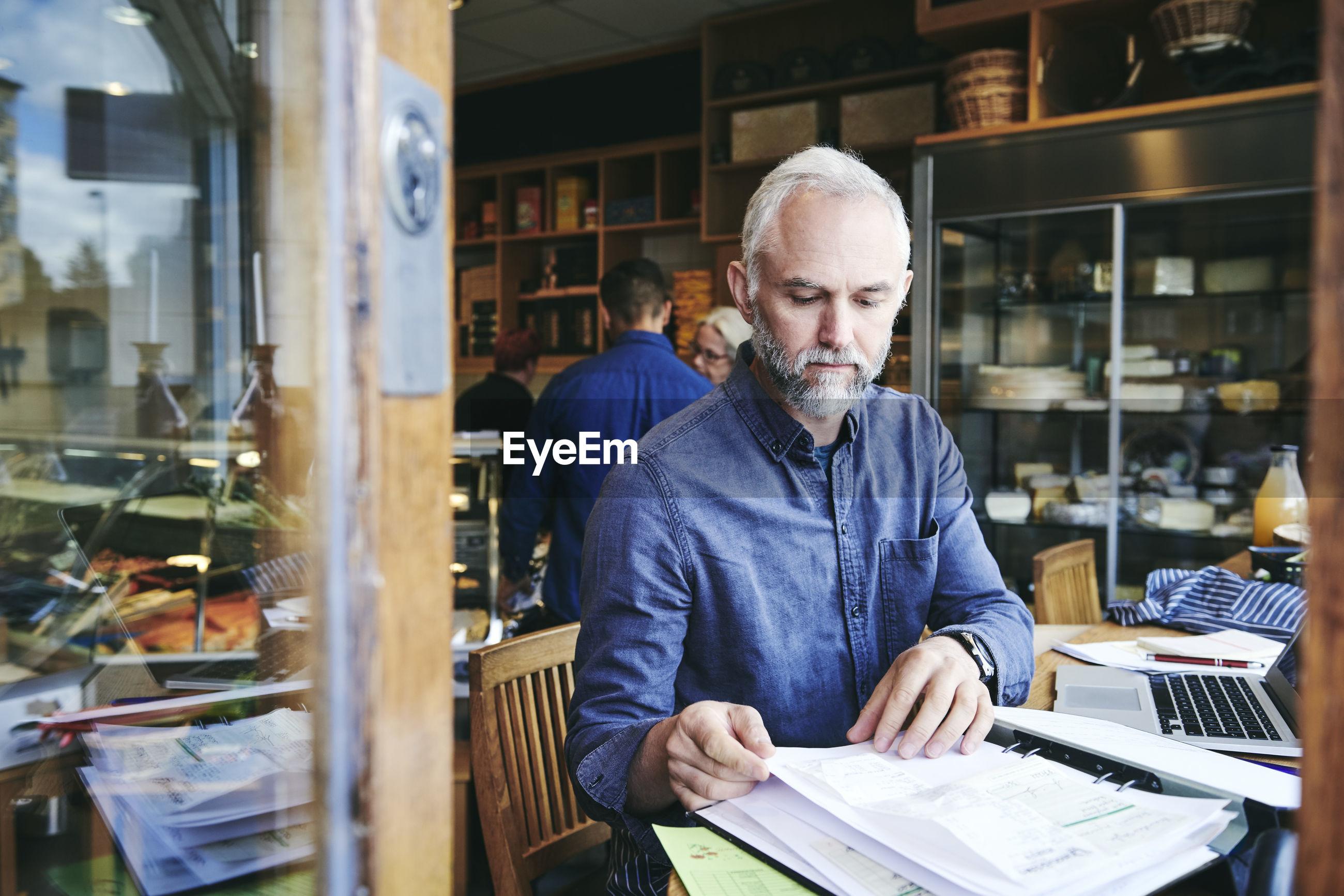 PORTRAIT OF A MAN WORKING IN OFFICE