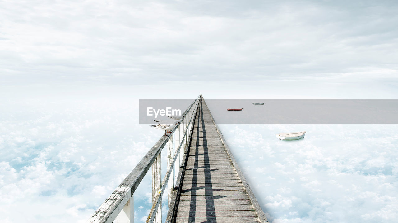 Digital composite image of pier and cloudy sky
