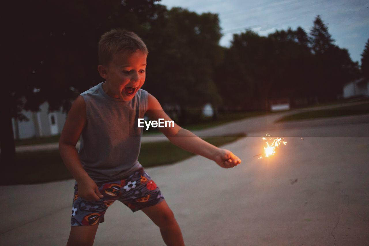 Boy holding sparkler at park during dusk