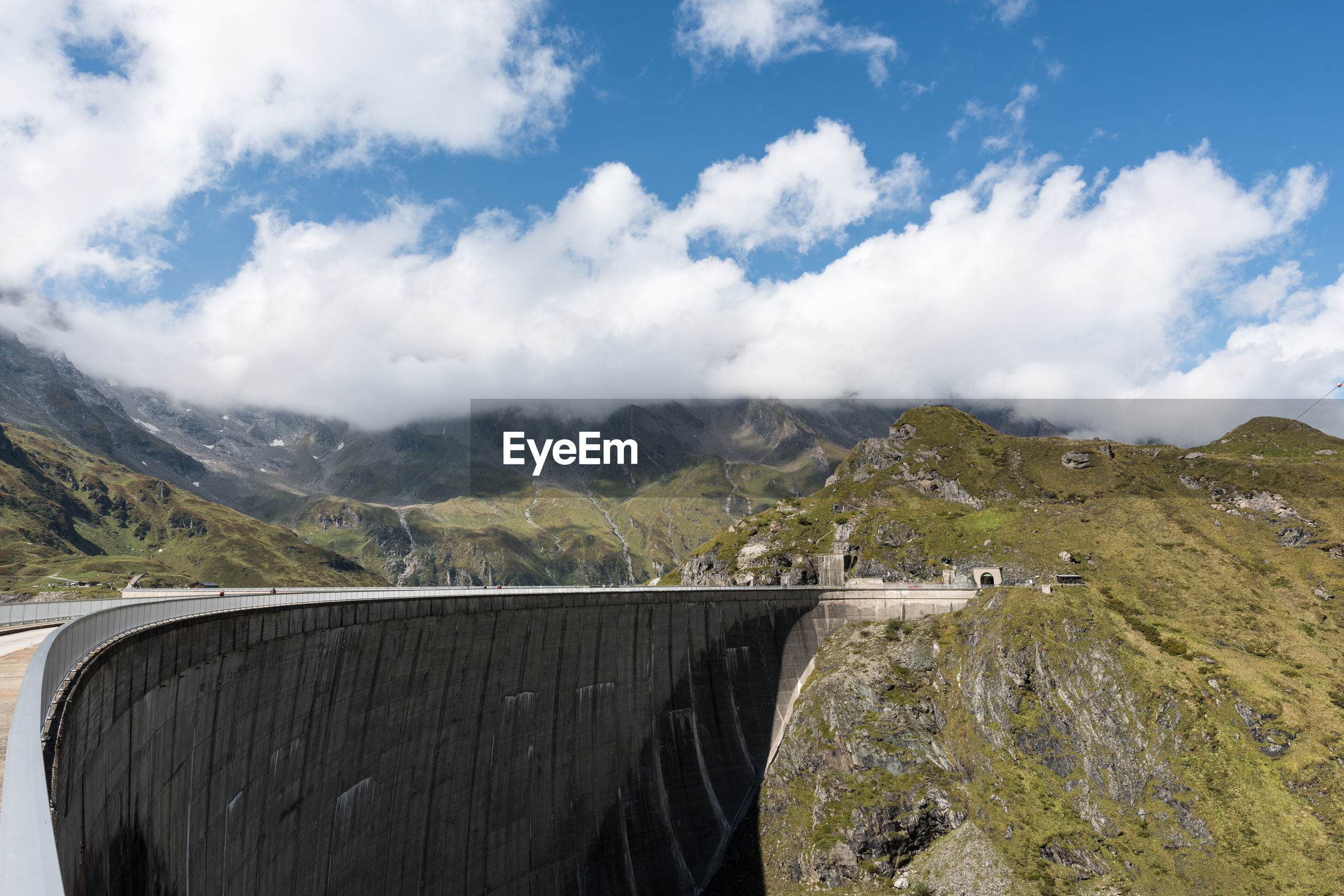 Scenic view of dam and mountains against cloudy sky