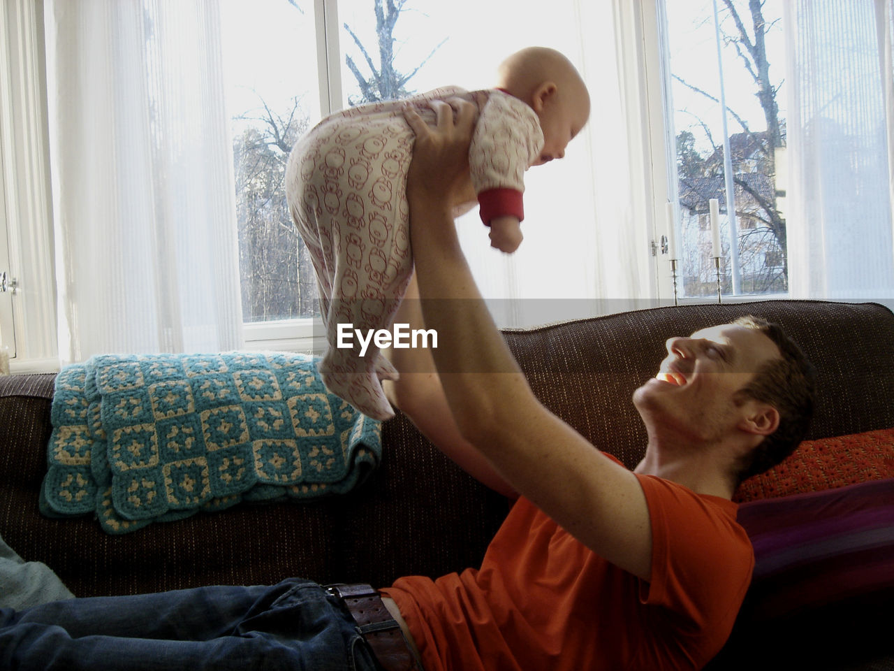 Father Lifting Baby Girl While Lying On Sofa
