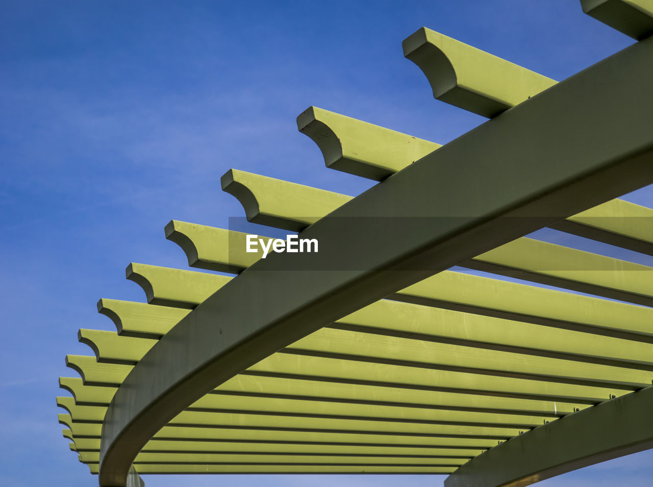 low angle view, sky, built structure, architecture, no people, blue, day, nature, pattern, sunlight, metal, building exterior, outdoors, roof, clear sky, building, design, yellow, green color, sunny