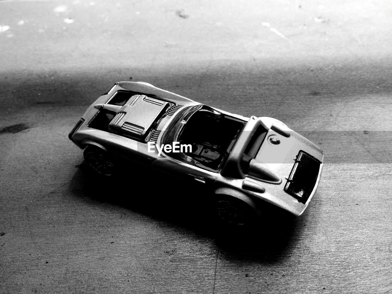 toy car, transportation, toy, high angle view, car, mode of transportation, no people, close-up, indoors, still life, single object, focus on foreground, land vehicle, table, motor vehicle, selective focus, day, retro styled, metal