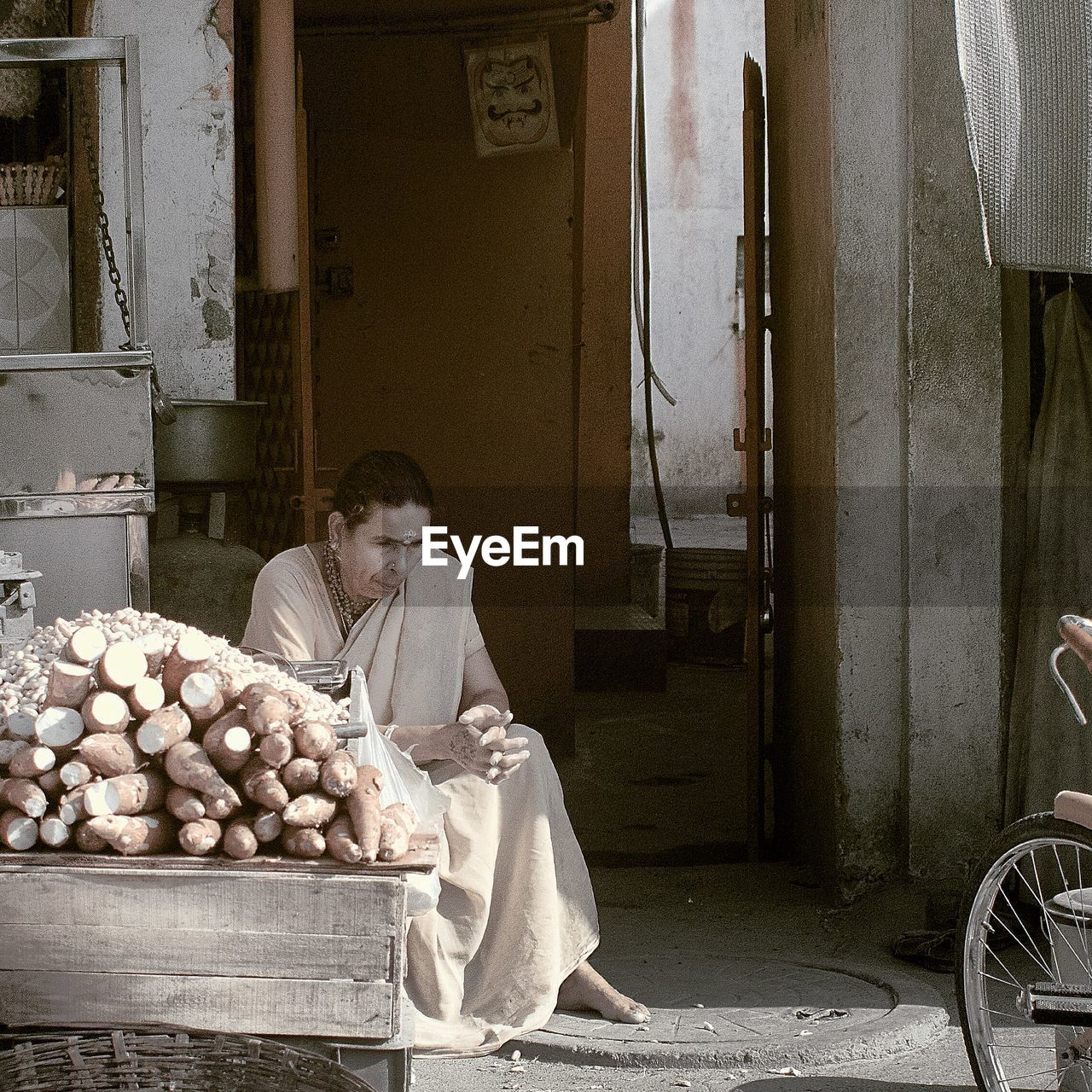 Mature Woman Selling Sweet Potatoes At Street Market