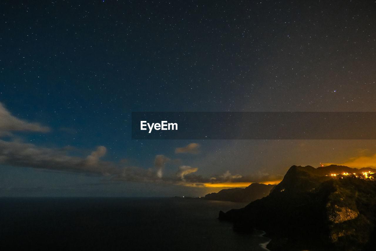 Scenic view of atlantic ocean against starry sky at night