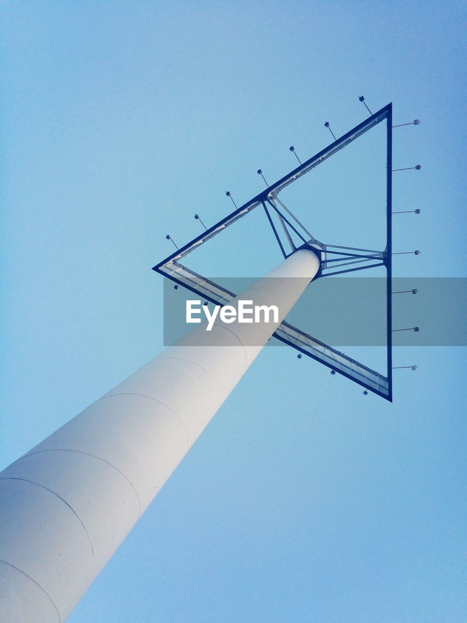 Low angle view of triangle shape billboard against clear blue sky