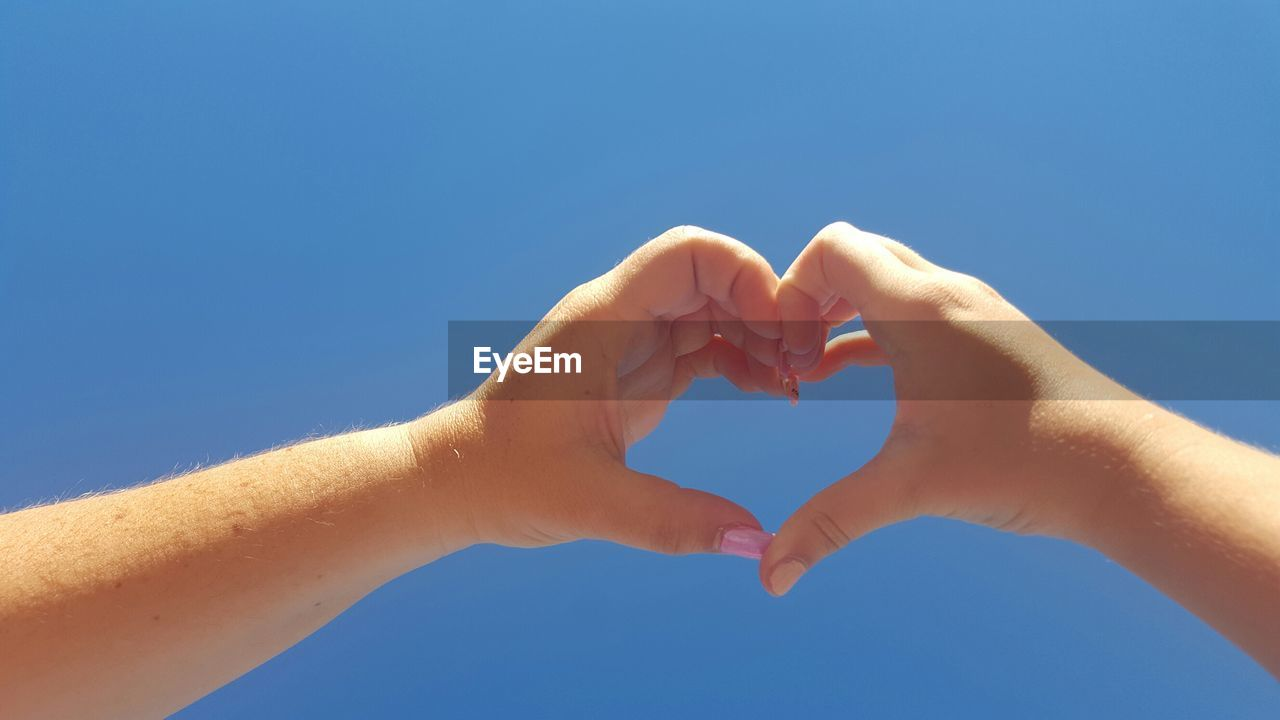 Close-up of hands showing heart shape against sky