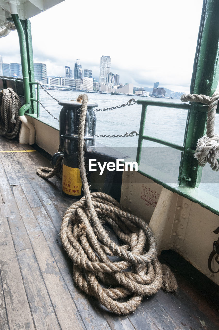 water, rope, transportation, nautical vessel, mode of transportation, no people, sea, day, sky, architecture, nature, harbor, city, built structure, close-up, travel, outdoors, bollard, strength, post, passenger craft, skyscraper