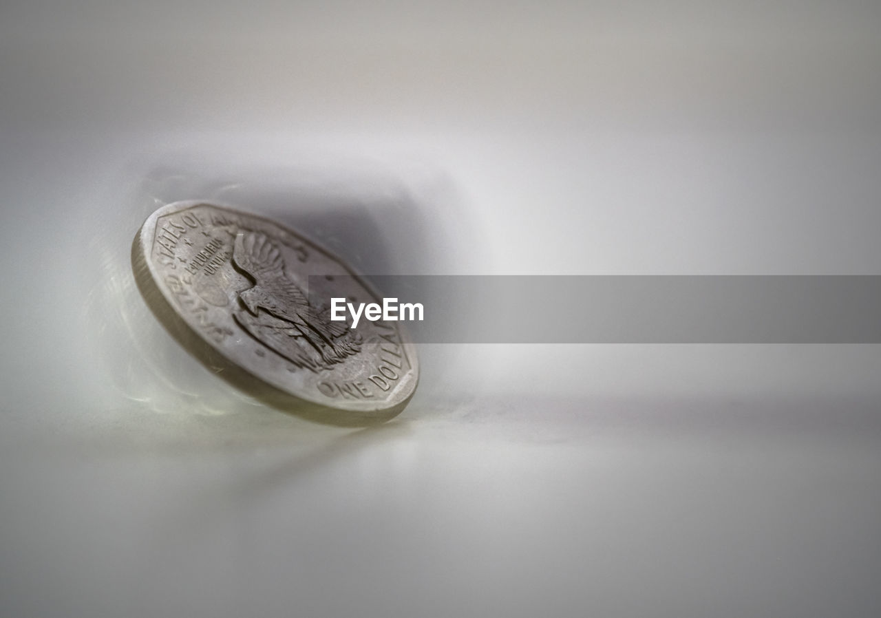 HIGH ANGLE VIEW OF COIN ON TABLE