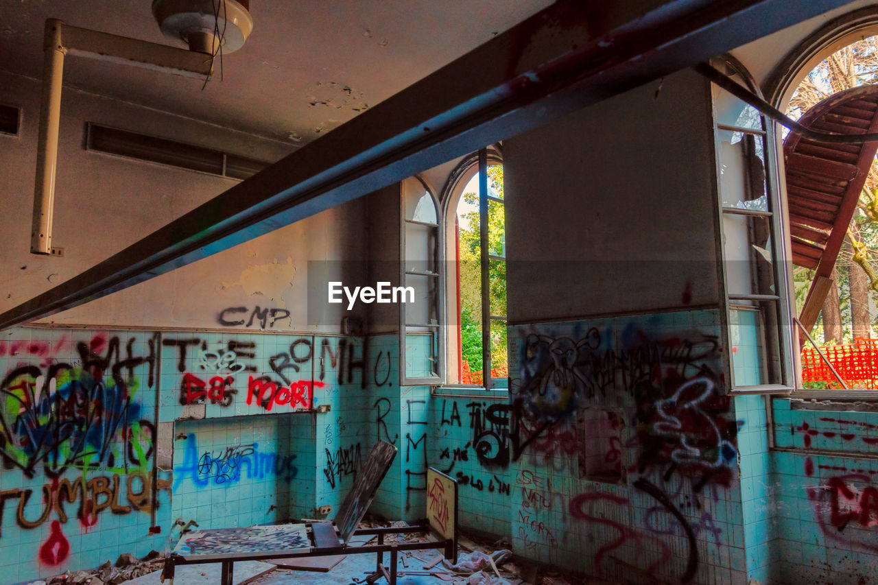 architecture, graffiti, built structure, no people, indoors, window, wall - building feature, text, building, abandoned, day, communication, creativity, messy, art and craft, damaged, empty, multi colored, ceiling