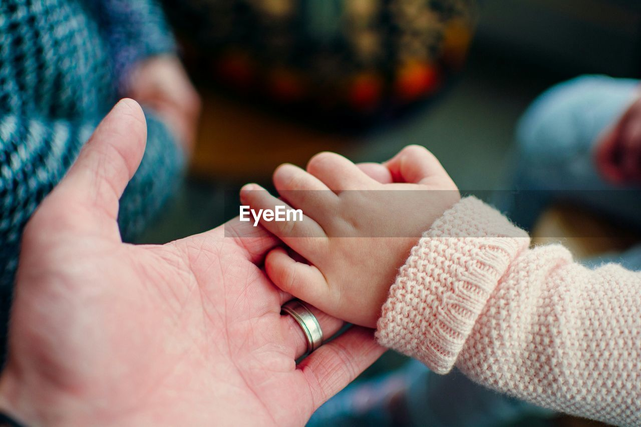 Extreme Close Up Of Hand Holding Baby Hand