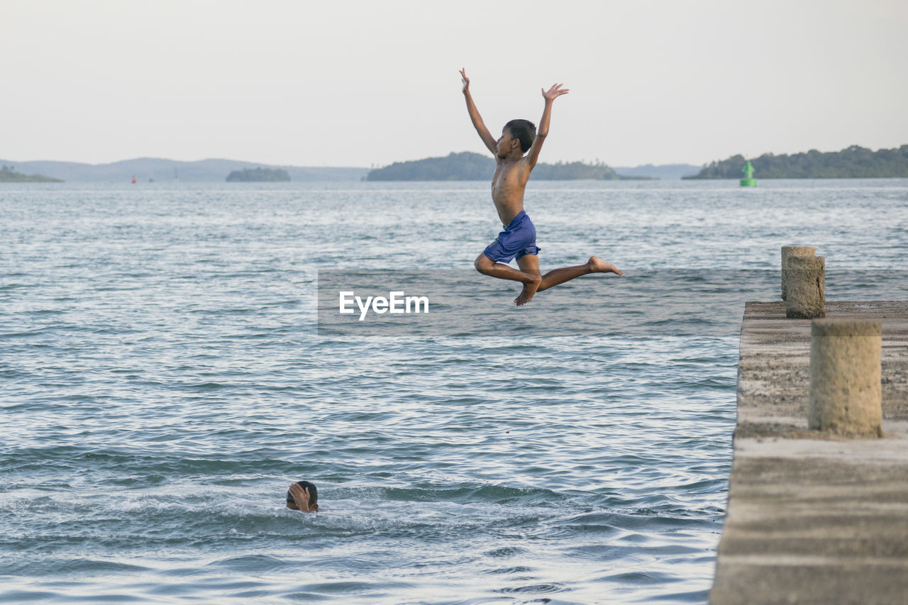 Full Length Of Shirtless Boy Jumping In Sea