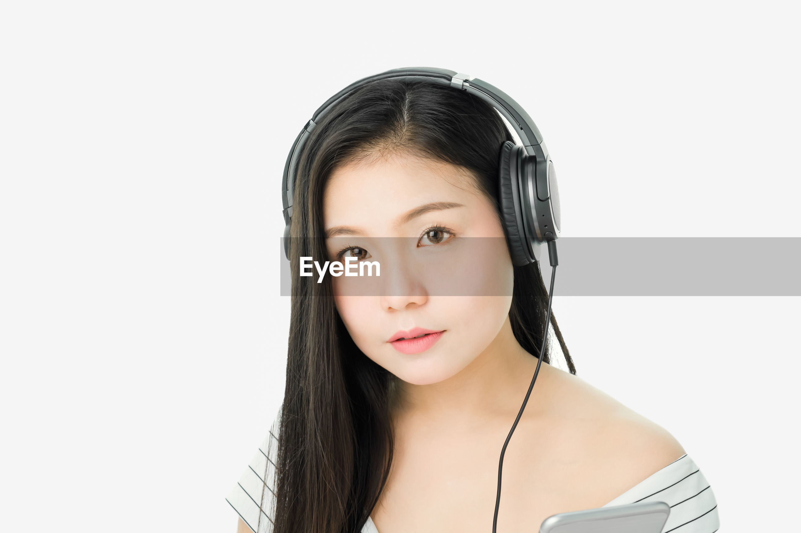 Portrait of young woman listening to music through headphones against white background