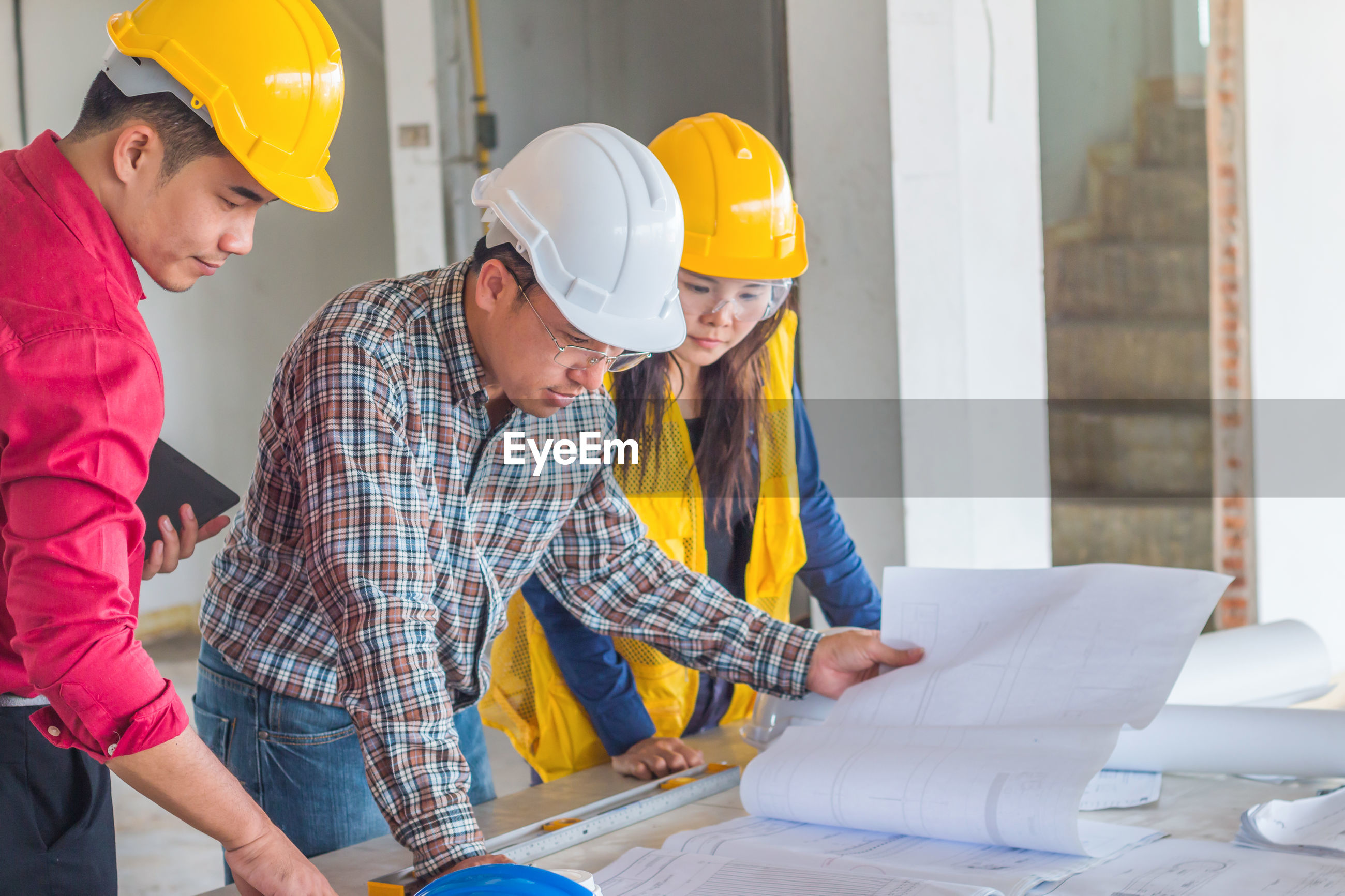 Architects working over blueprints at construction site