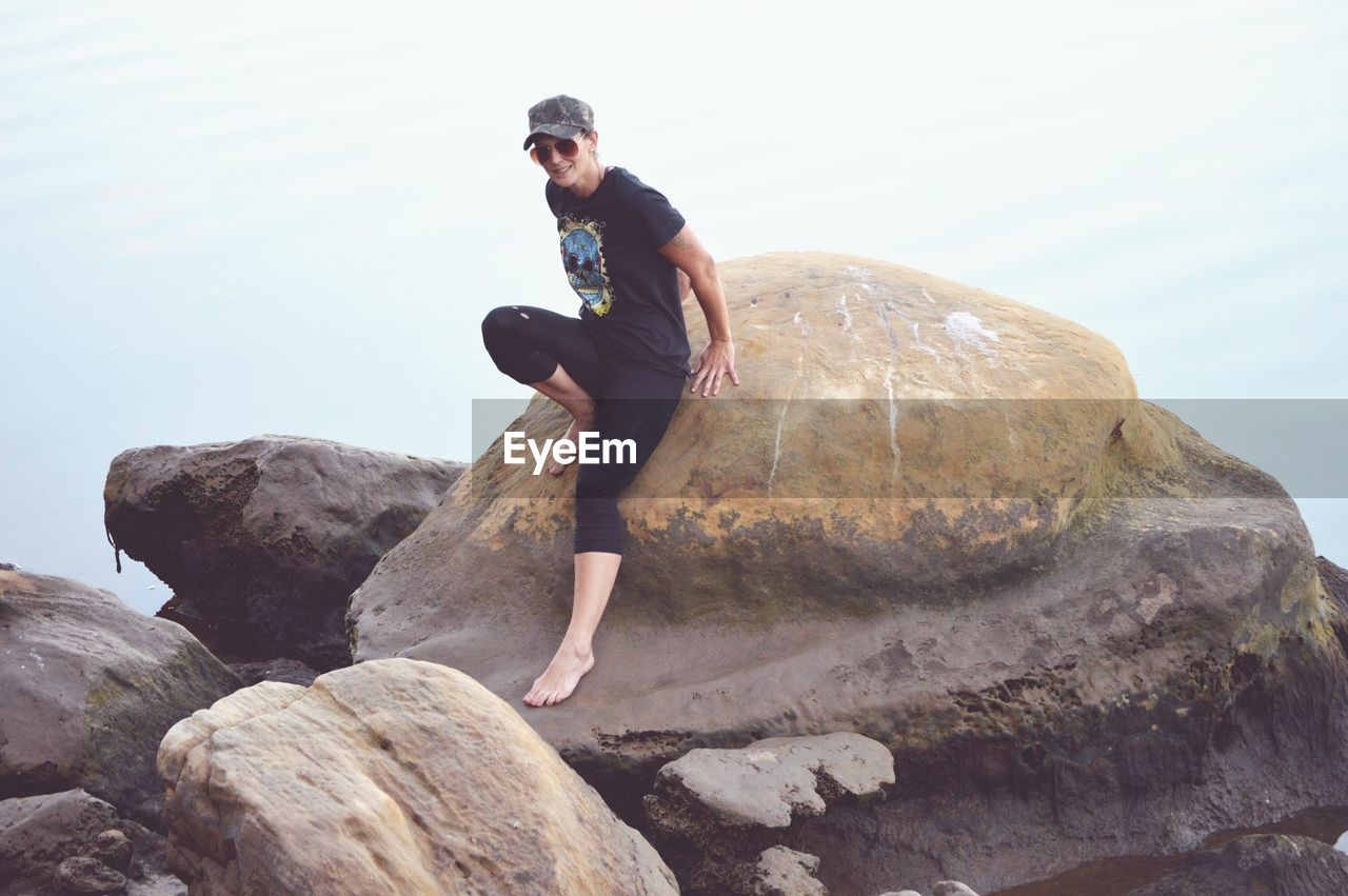 Woman sitting on boulder against sky