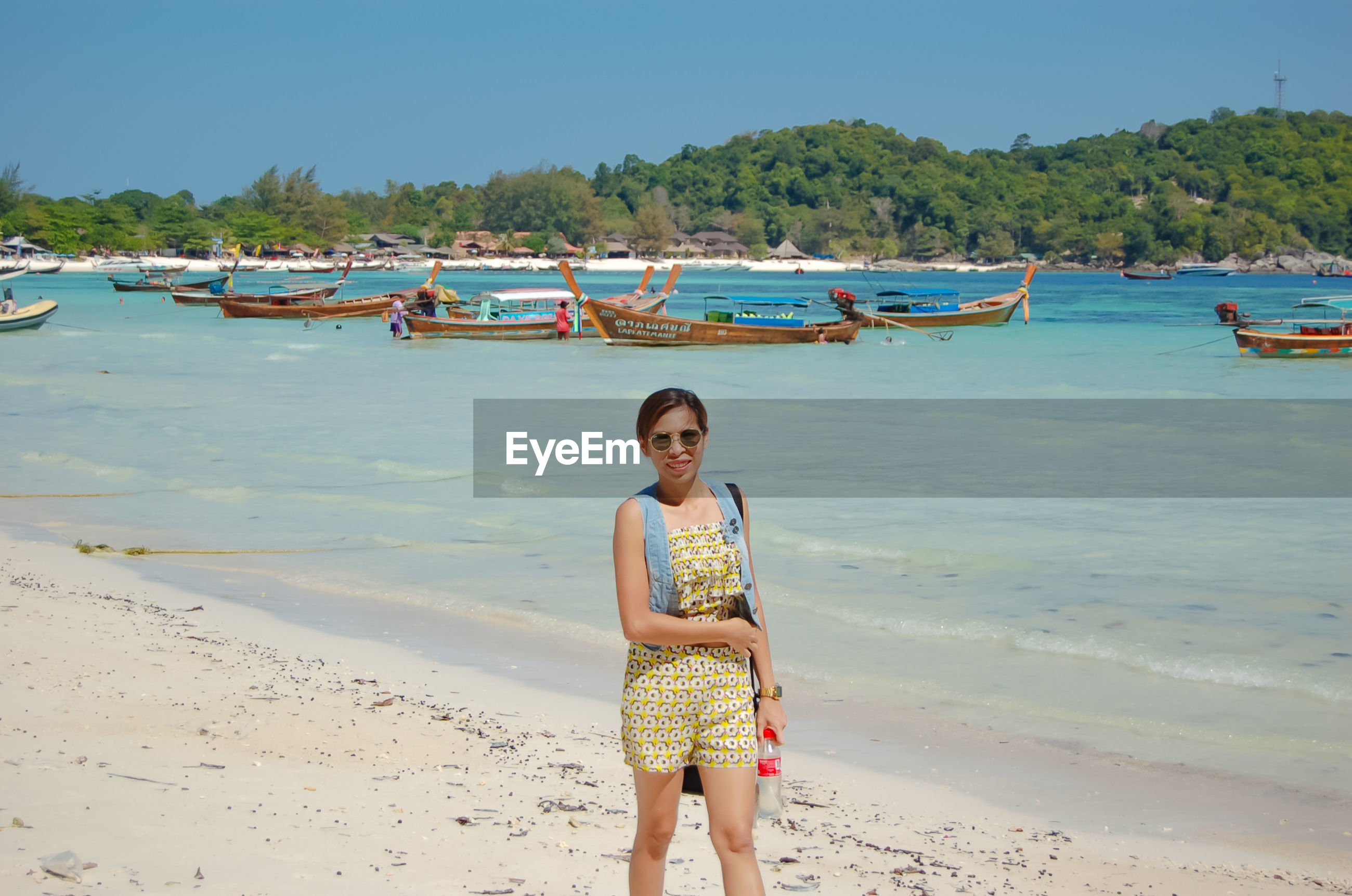 Portrait of woman in sunglasses walking at beach