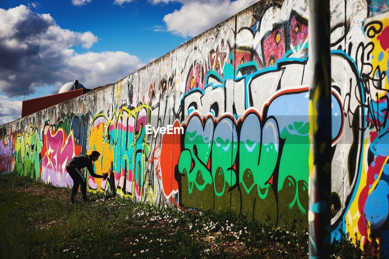 GRAFFITI ON WALL AGAINST CLOUDY SKY