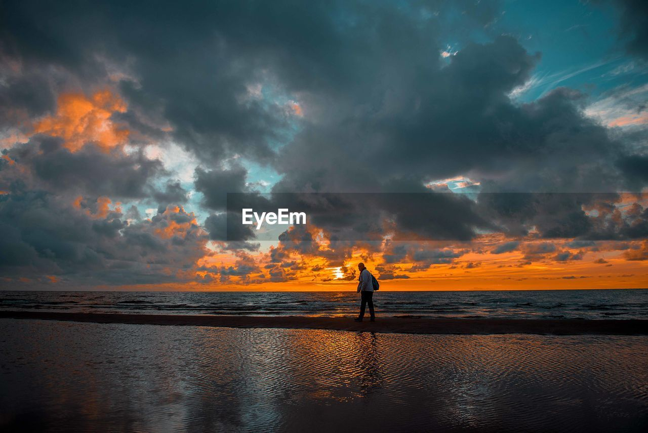 sky, cloud - sky, sunset, water, scenics - nature, beauty in nature, sea, silhouette, horizon over water, real people, beach, horizon, land, orange color, tranquility, one person, nature, standing, tranquil scene, outdoors