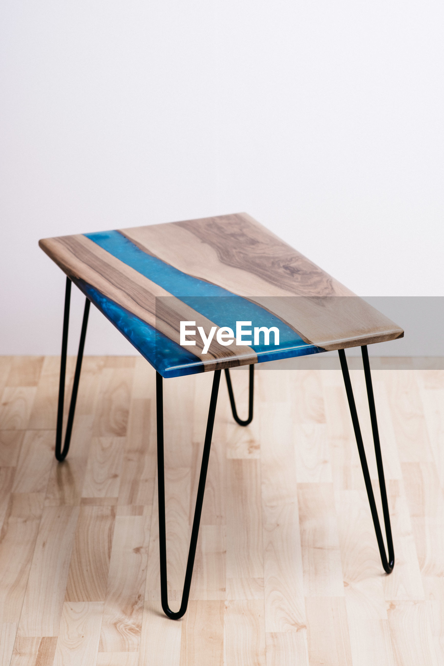 EMPTY CHAIR ON TABLE AGAINST BLUE WALL