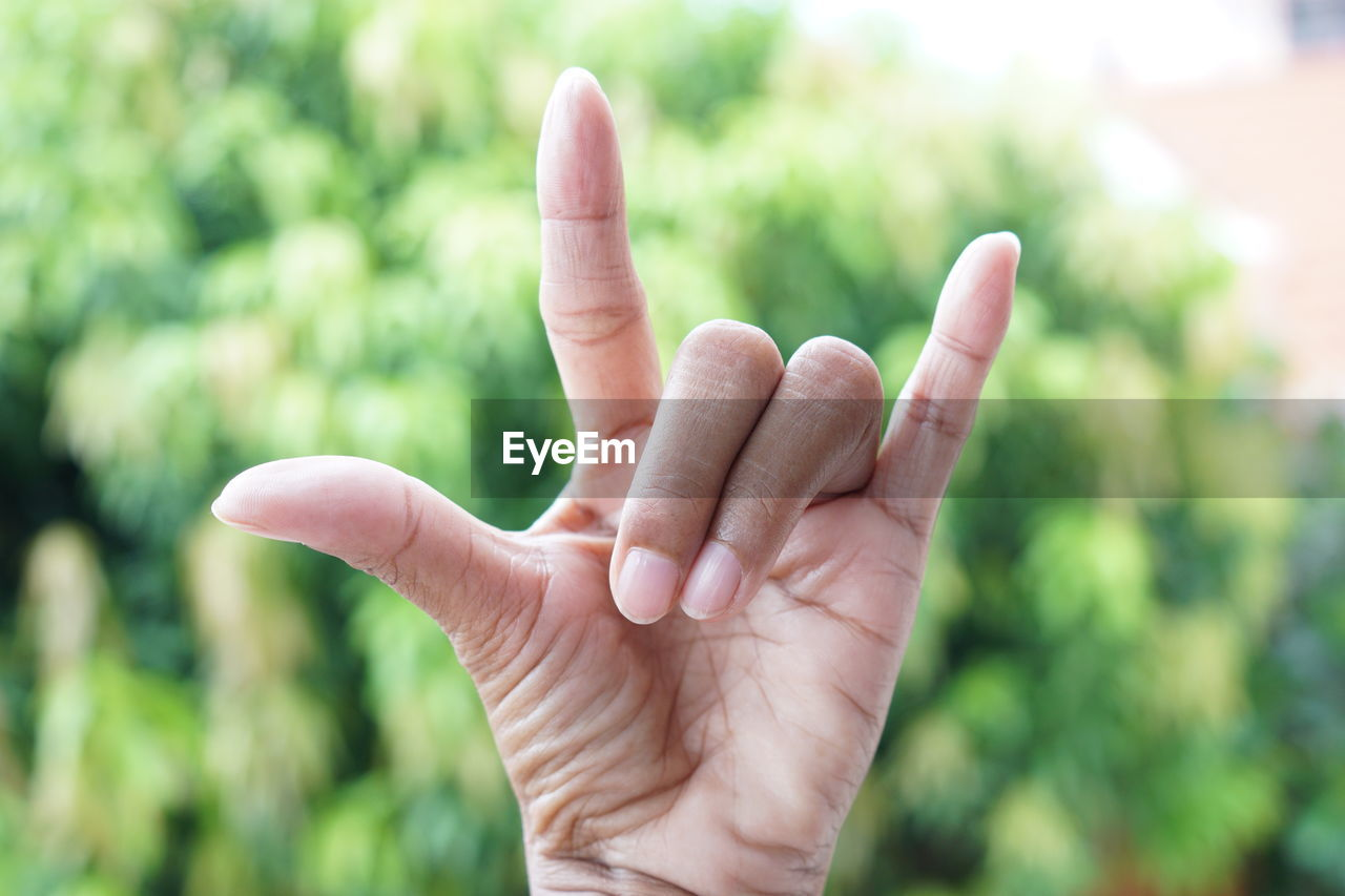 human hand, hand, human body part, finger, human finger, gesturing, body part, focus on foreground, real people, one person, unrecognizable person, hand sign, day, close-up, lifestyles, showing, outdoors, men, thumb, human limb, obscured face