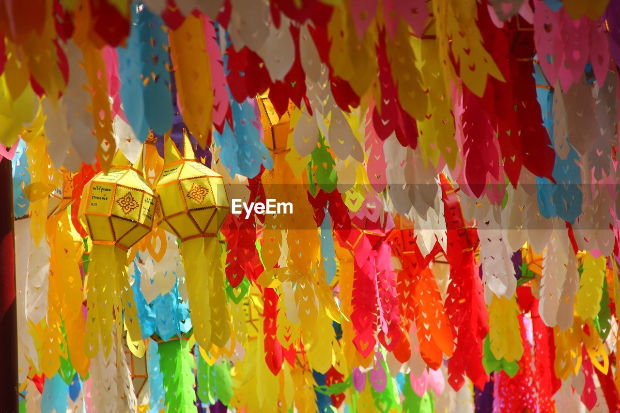 multi colored, no people, art and craft, hanging, decoration, close-up, creativity, day, focus on foreground, craft, full frame, backgrounds, outdoors, pattern, low angle view, yellow, representation, celebration, floral pattern