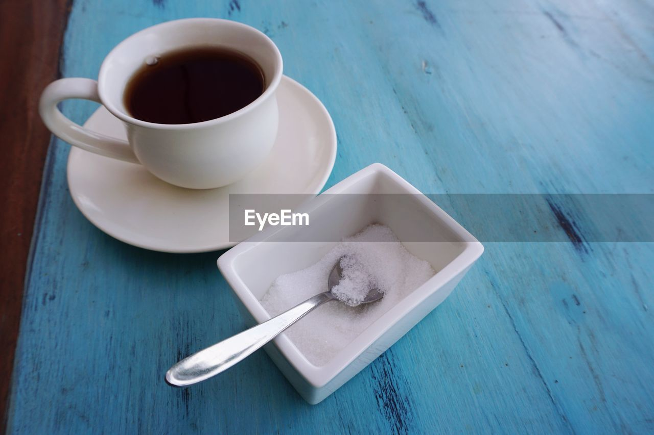 High angle view of coffee cup in plate on table