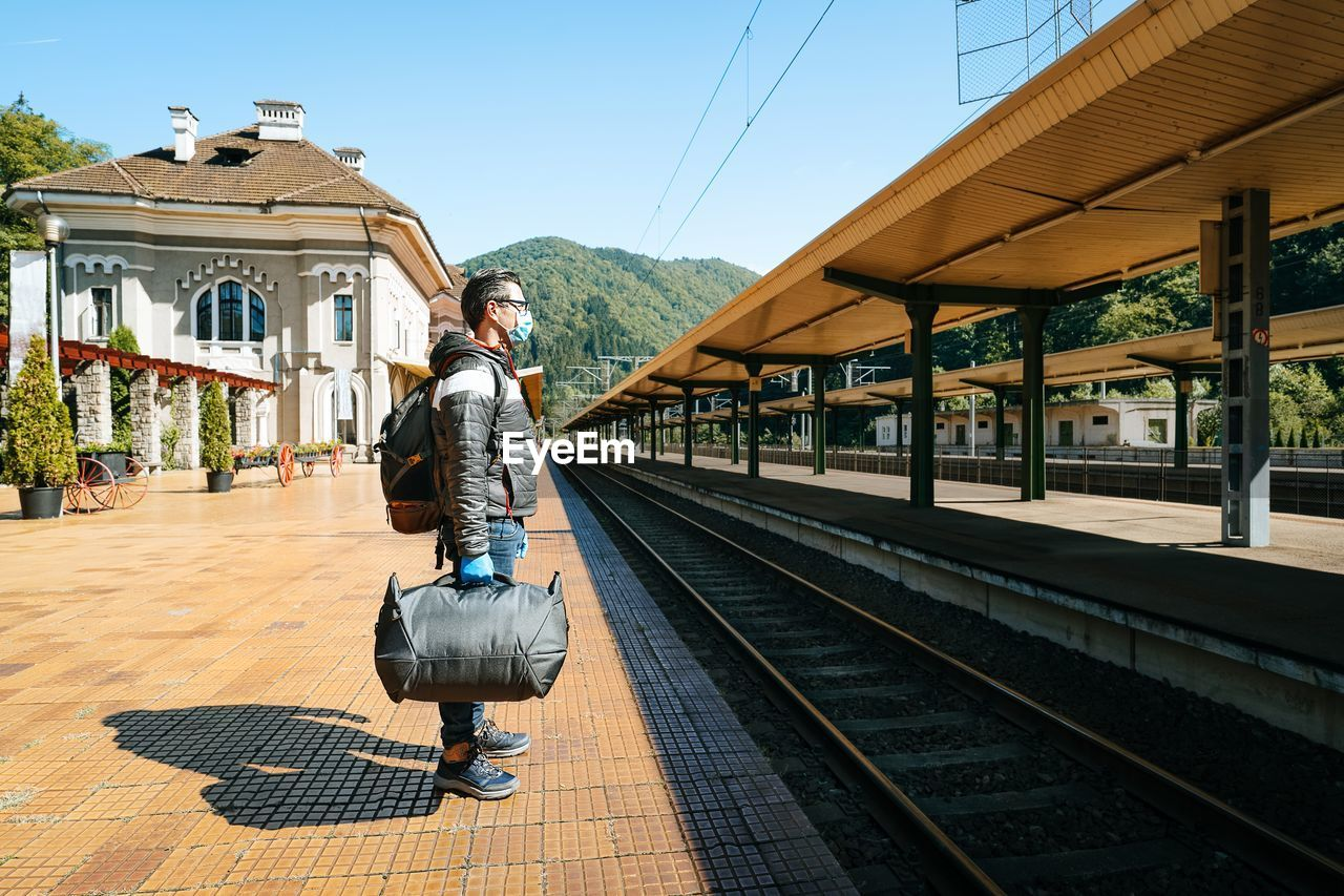 People with mask on railroad station against mountains and sky