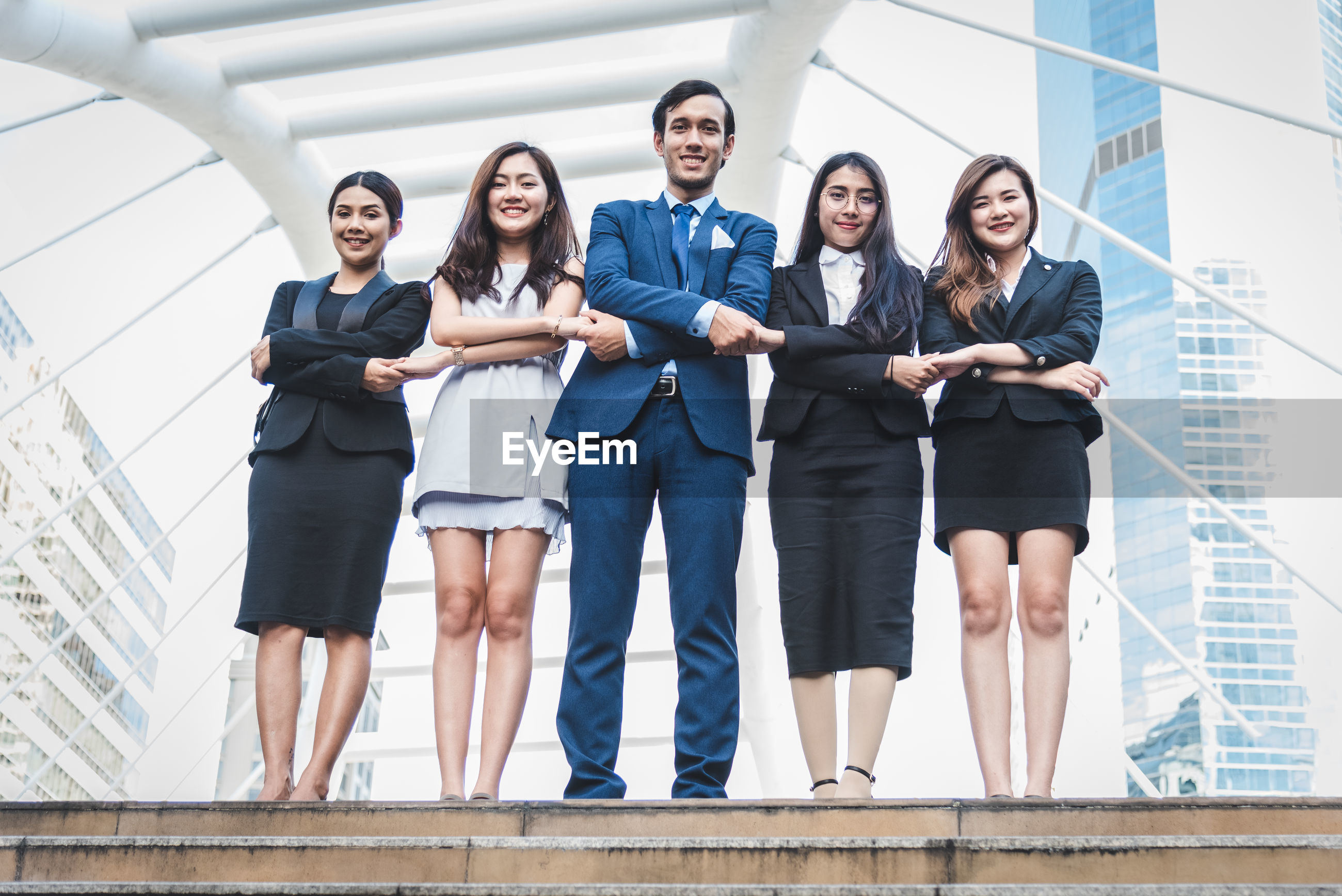 Full length portrait of smiling business people holding hands while standing outdoors