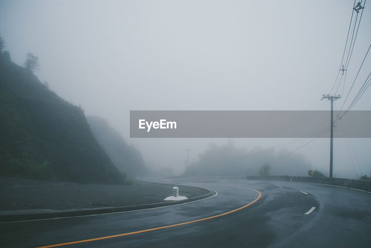fog, transportation, road, the way forward, foggy, weather, mountain, connection, mist, outdoors, nature, day, no people, tranquility, electricity pylon, beauty in nature, sky