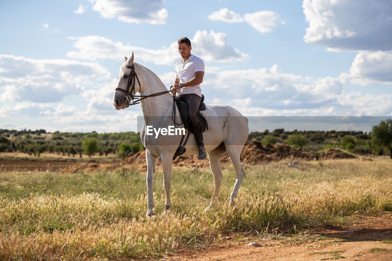 Man sitting on horse against sky