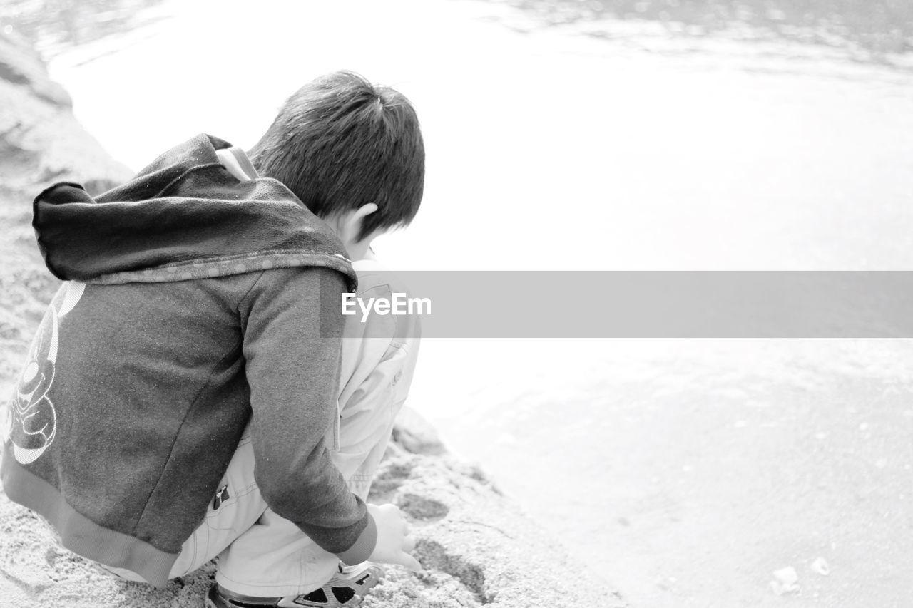 Rear View Of Boy Playing At Lakeshore