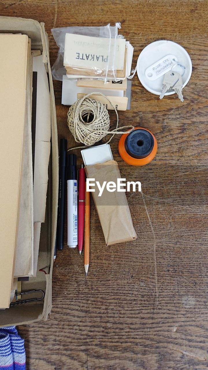 table, high angle view, indoors, wood - material, directly above, no people, still life, paper, pen, textile, art and craft, scissors, thread, publication, book, tape measure, medium group of objects, creativity, choice, spool